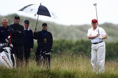 Real estate magnate Donald Trump (R) plays golf during the opening of his Trump International Golf Links golf course near Aberdeen, northeast Scotland in this file photo taken on July 10, 2012. REUTERS/David Moir