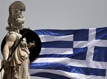 Una bandera nacional griega junto a una estatua de la diosa Atenea, en Atenas, el 21 de mayo de 2015. Grecia podría evitar pagar al FMI el 5 de junio y ganar más tiempo para negociar un acuerdo de financiamiento sin caer en moratoria, si agrupa todos los pagos al organismo que vencen en junio y los desembolsa a fines de ese mes, dijeron el martes funcionarios del bloque. REUTERS/Alkis Konstantinidis