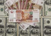 Рублевые и долларовые купюры. Сараево, 9 марта 2015 года. Рубль подорожал против доллара утром среды на фоне отрицательной динамики валюты США и роста нефтяных цен на мировых рынках, поддержкой могут выступать продажи оставшейся под уплату налога на прибыль экспортной выручки. REUTERS/Dado Ruvic