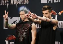 Tyler Joseph (R) and Josh Dun of Twenty One Pilots pose during the 2014 MTV Movie Awards in Los Angeles, California  April 13, 2014.  REUTERS/Danny Moloshok