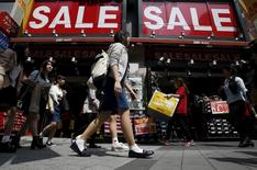 A shop clerk (2nd R) carries a box of shoes under sale signboards at a shoes retail store at a shopping district in Tokyo, Japan, April 28, 2015. REUTERS/Yuya Shino
