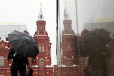 Мужчина с зонтом у Красной площади в Москве. 18 мая 2011 года. Выходные в Москве будут теплыми, но дождливыми, свидетельствует усреднённый прогноз, составленный на основании данных Гидрометцентра России, сайтов intellicast.com и gismeteo.ru. REUTERS/Denis Sinyakov