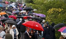 Visitors carry umbrellas past the Laurent-Perrier Chatsworth Garden during a rain storm at the Royal Horticultural Society's Chelsea Flower Show in London, Britain May 19, 2015.  REUTERS/Suzanne Plunkett