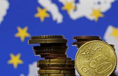 Монеты евро на фоне флага и карты ЕС. Зеница, 28 мая 2015 года. Евро снижается в понедельник после того, как Греция пропустила ею самой установленный крайний срок для достижения соглашения о помощи с кредиторами. REUTERS/Dado Ruvic
