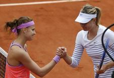 Lucie Safarova of the Czech Republic (L) shakes hands with Maria Sharapova of Russia after winning their women's singles match during the French Open tennis tournament at the Roland Garros stadium in Paris, France, June 1, 2015.  REUTERS/Jean-Paul Pelissier