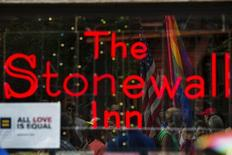 People celebrating the U.S. Supreme Court ruling against the Defense of Marriage Act can be seen reflected in the window of the Stonewall Inn in New York June 26, 2013.  REUTERS/Lucas Jackson