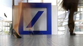Personas caminan junto al logo de Deutsche Bank antes de la reunión anual de bancos, en Fráncfort, el 21 de mayo de 2015. Deutsche Bank lanzará tres innovadores laboratorios este año, en colaboración con grandes firmas de desarrollo para acelerar la creación de tecnología financiera para usos propios e invertirá hasta 1.000 millones de euros en desarrollo digital en los próximos cinco años. REUTERS/Kai Pfaffenbach/Files