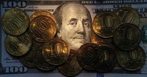 Рублевые монеты на долларовой купюре в Санкт-Петербурге 22 октября 2014 года. Рубль при открытии биржевых торгов четверга обновил многонедельные минимумы в условиях обострения ситуации на востоке Украины, а также при сохранении текущих неблагоприятных для рубля факторов: намерений Центробанка увеличивать свои резервы и отмены регулятором годового валютного рефинансирования, а также ожиданий снижения ключевой ставки ЦБ в середине июня. REUTERS/Alexander Demianchuk