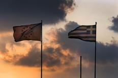 Grecia quiere seguir buscando un terreno común con sus prestamistas de la Unión Europea y el Fondo Monetario Internacional, dijo el domingo un funcionario gubernamental, mientras se acaba el tiempo para evitar que el país heleno se quede sin liquidez. Una bandera de la Unión Europea ondea junto a la de Grecia en el Ministerio de Finanzas griego durante la puesta de sol en el centro de Atenas. 5 junio 2015. REUTERS/Yannis Behrakis