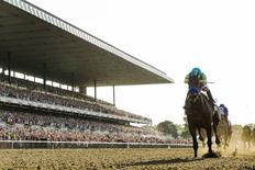 Jockey Victor Espinoza, aboard American Pharoah, crosses the finish line as he wins the 147th running of the Belmont Stakes as well as the Triple Crown, in Elmont, New York, June 6, 2015. REUTERS/Lucas Jackson