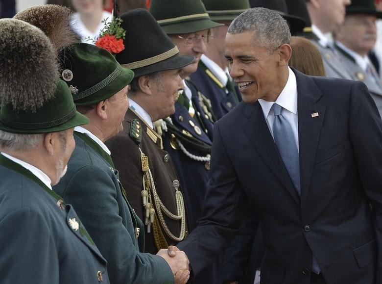 U.S. President Barack Obama (R) shakes hands with people in traditional Bavarian clothes during a welcoming ceremony in Munich airport in Germany, June 7, 2015.  REUTERS/Lukas Barth