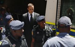 Velocista olímpico e paralímpico Oscar Pistorius é escoltado pela polícia em Pretória. 21/10/2014 REUTERS/Siphiwe Sibeko