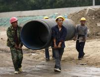 Рабочие несут трубу на месте строительства новой дороги под Пекином. 13 мая 2015 года. Экономисты китайского Центробанка снизили прогноз роста экономики в 2015 году до 7,0 процента с 7,1 процента, указав на увеличивающееся понижательное давление на активность. REUTERS/Kim Kyung-Hoon