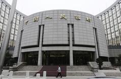 Una persona camina frente a la sede del Banco Popular Chino, en Beijing, 25 de junio de 2013. Economistas del banco central chino redujeron fuertemente sus pronósticos para la inflación del país en 2015 y predijeron un repunte de la segunda economía más grande del mundo durante los próximos seis meses, gracias a una estabilización en los precios de las viviendas y una demanda externa más firme. REUTERS/Jason Lee (CHINA - Tags: BUSINESS)