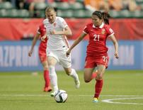 June 11, 2015; Edmonton, Alberta, CAN; China PR midfielder Wang Lisi (21) moves the ball against Netherlands defender Petra Hogewoning (5) during the second half in a Group A soccer match in the 2015 FIFA women's World Cup at Commonwealth Stadium. Mandatory Credit: Erich Schlegel-USA TODAY Sports  - RTX1G5JJ