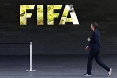A staff walks past a logo of soccer's international governing body FIFA at their headquarters in Zurich, Switzerland, May 27, 2015.  REUTERS/Ruben Sprich/Files
