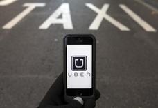Foto ilustração do logotipo do Uber diante de uma faixa reservada para táxis, em Madri. 10/12/2014 REUTERS/Sergio Perez