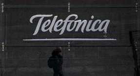 El reflejo de un hombre hablando por su celular afuera de una tienda principal de Telefonica en el centro de Madrid, España, 28 de abril de 2015. Los ingresos del grupo Telefónica en España subieron en mayo en términos interanuales por primera vez en seis años luego de una prolongada crisis económica, dijo el viernes el presidente de la compañía, después de un alza de las tarifas aplicada el mes pasado. REUTERS/Sergio Perez