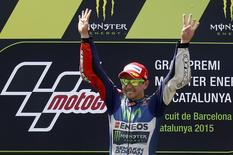 Yamaha MotoGP rider Jorge Lorenzo of Spain gestures the number 4 while celebrating his victory in the Catalunya Grand Prix in Montmelo, near Barcelona, Spain June 14, 2015. REUTERS/Albert Gea