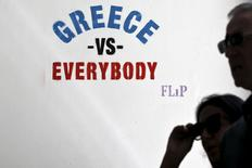 """Personas caminan junto a un stencil que dice """"Grecia contra todos"""", hecho por el artista callejero """"Flip"""", en Atenas, 4 de junio de 2015. El comisario europeo de Alemania dijo el lunes que era tiempo de prepararse para un """"estado de emergencia"""" tras el colapso de las conversaciones el fin de semana para rescatar a Grecia de un default y de una salida de la zona euro. REUTERS/Alkis Konstantinidis"""