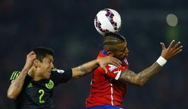 Arthuro Vidal, do Chile, cabeceia a bola marcado pelo mexicano Julio Domínguez em partida da Copa América. 15/06/2015 REUTERS/Ivan Alvarado