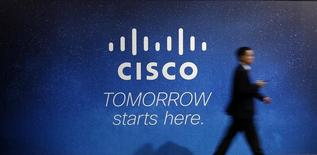 A visitor walks past a Cisco advertising panel at the Mobile World Congress in Barcelona February 27, 2014. REUTERS/Albert Gea