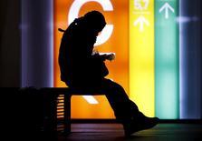 Una mujer revisa su teléfono móvil en el distrito financiero de Tokio, abr 30 2015. Investigadores de seguridad han descubierto una falla en el almacenamiento de miles de aplicaciones móviles, dejando la información personal de los usuarios, incluyendo contraseñas, direcciones, códigos de acceso y datos de ubicación, al alcance de los hackers. REUTERS/Yuya Shino