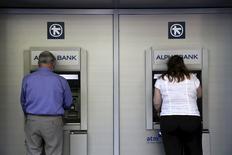 Unas personas utilizando cajeros automáticos en una sucursal del banco Alpha en Atenas, jun 3 2015. Los bancos griegos han detectado un aumento de la salida de depósitos a unos 2.000 millones de euros en los últimos tres días, y el ritmo de los retiros se ha triplicado desde el colapso de las negociaciones de Atenas con los acreedores de la zona euro, dijeron el jueves a Reuters fuentes del sector.  REUTERS/Alkis Konstantinidis