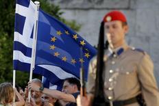 """Unas personas sostienen una bandera de Grecia a las afueras del Parlamento en Atenas, jun 18 2015. Un informe del diario alemán Die Zeit publicado el jueves sobre posibles concesiones a Grecia por parte de sus acreedores internacionales """"no tiene nada que ver con la realidad"""", dijeron a Reuters diplomáticos de la Unión Europea.  REUTERS/Yannis Behrakis"""
