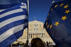 Mulheres com bandeiras da UE e da Grécia do lado de fora do Parlamento grego, em Atenas. 18/06/2015 REUTERS/Yannis Behrakis