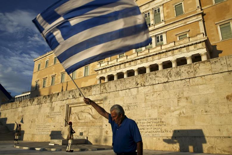 A man waves a Greek national flag as Greek presidential guards conduct their ceremonial march during a rally outside the parliament, calling on the government to clinch a deal with its international creditors and secure Greece's future in the Eurozone, in Athens June 18, 2015. REUTERS/Yannis Behrakis