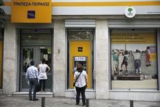 Personas hacen transacciones en una máquina ATM, mientras otros esperan para entrar a una sucursal del banco Piraeus, en Atenas, Grecia, 19 de junio de 2015. Los ahorradores griegos sacaron más de 1.000 millones de euros de los bancos de su país el jueves, dijeron a Reuters tres fuentes bancarias de alto rango, y el ritmo de los retiros ha ganado velocidad desde que las negociaciones entre el Gobierno y sus acreedores colapsaron la semana pasada. REUTERS/Alkis Konstantinidis