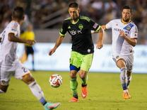 Oct 19, 2014; Carson, CA, USA; Seattle Sounders FC forward Clint Dempsey (2) moves the ball between Los Angeles Galaxy defender A.J. DeLaGarza (20) and Los Angeles Galaxy defender Dan Gargan (33) during seconds half action at StubHub Center. Mandatory Credit: Robert Hanashiro-USA TODAY Sports