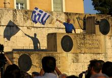 A protester waves a Greek flag at the entrance of the Greek parliament, during a rally calling on the government to clinch a deal with its international creditors and secure Greece's future in the Eurozone, in Athens, June 18, 2015. REUTERS/Yannis Behrakis