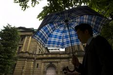 A man holds umbrella as they walk past the Bank of Japan (BOJ) building on a rainy day in Tokyo June 19, 2015.  REUTERS/Thomas Peter