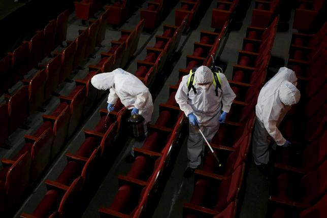 Employees from a disinfection service company sanitize the interior of a theater in Seoul, South Korea, June 18, 2015.  REUTERS/Kim Hong-Ji
