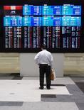 Un hombre mira una pantalla que muestra los índices de mercado en la Bolsa de Tokyo, 11 de junio de 2015. Las bolsas de Asia comenzaban la semana con un avance y el euro se fortalecía el lunes, después de que Grecia se apresuró a evitar el impago de su deuda con unas propuestas de última hora destinadas a apaciguar a sus acreedores. REUTERS/Thomas Peter