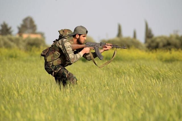 A rebel fighter aims his weapon as he takes a position during a military training in Aleppo's countryside against forces loyal to Syria's President Bashar al-Assad April 20, 2015. REUTERS/Jalal Al-Mamo