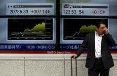 Un hombre parado frente a un tablero electrónico que muestra el índice Nikkei y la tasa de cambio entre el yen japonés y el dólar estadounidense, afuera de una agencia de la bolsa, en Tokyo, Japón, 23 de junio de 2015. El índice Nikkei de la bolsa de Tokio subió el martes a un nuevo máximo en 15 años por las esperanzas de un avance en las negociaciones sobre la deuda griega. REUTERS/Yuya Shino