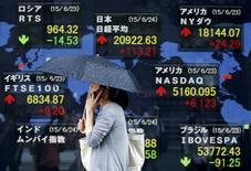 Женщина у брокерской конторы в Токио. 24 июня 2015 года. Азиатские фондовые рынки выросли в среду за счет надежды инвесторов на соглашение Греции с кредиторами и местных факторов. REUTERS/Issei Kato