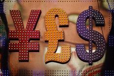 Символы валют иена, фунт стерлингов и доллар в Гонконге 30 октября 2014 года. Курс доллара к иене снижается накануне выхода экономической статистики США. REUTERS/Damir Sagolj  TO FIND ALL IMAGES SEARCH 'CURRENCY TRADERS'