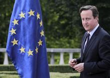 El primer ministro británico, David Cameron, camina junto a una bandera de la Unión Europea, en una visita a Eslovenia, 18 de junio de 2015. La posibilidad de que Reino Unido abandone la Unión Europea en el futuro preocupa mucho más a los banqueros europeos que la perspectiva de que Grecia haga lo mismo antes. REUTERS/Srdjan Zivulovic
