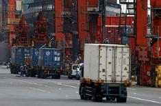 People work near cargo containers loaded from trucks at a port in Tokyo, June 17, 2015. REUTERS/Yuya Shino