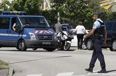 Жандарм закрывает проезд к промзоне в Сен-Кантен-Фаллавье. 26 июня 2015 года. Неизвестные въехали на автомобиле на территорию предприятия, принадлежащего американской газовой компании, на юго-востоке Франции в пятницу и устроили взрыв, убив одного и ранив нескольких человек, сообщили источники в полиции и местные СМИ. REUTERS/Emmanuel Foudrot