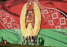 Гигантский плакат с флагом и гербом Белоруссии в Минске. 3 июля 2014 года. Белоруссия планирует перенести размещение еврооблигаций на сумму от $1 миллиарда на начало 2016 года, а в июле ждет миссию МВФ для переговоров о новой программе финансирования, рассчитывая на кредит в размере порядка $3,5 миллиарда, сказал журналистам министр финансов Владимир Амарин. REUTERS/Vasily Fedosenko