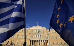 Manifestantes sostienen una bandera de la Unión Europea y una de Grecia, frente al parlamento en Atenas, 18 de junio de 2015. La zona euro puede ayudar a Grecia a pagar su deuda con dinero que aún tiene disponible bajo el rescate vigente, si el programa es extendido por cinco meses hasta noviembre, según una nota preparada para los ministros de Finanzas de la zona euro. REUTERS/Yannis Behrakis