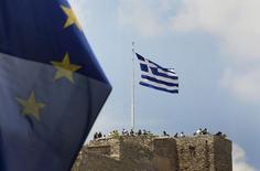 Una bandera de la Unión Europea, mientras turistas se juntan al rededor de una bandera de Grecia, sobre la Acrópolis en Atenas, Grecia, 26 de junio de 2015. La deuda griega incumplirá las metas fijadas por los acreedores en 2012, pero un análisis preparado para ministros de Finanzas de la zona euro muestra que el peso de la deuda aún es sustentable sin tener que amortizar buena parte de ella, si Grecia obtiene otro rescate a tres años. REUTERS/Yannis Behrakis