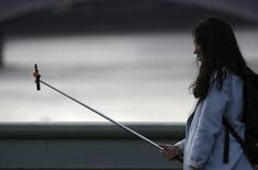 "A woman takes a photo using a ""selfie"" stick whilst standing on Westminster Bridge in London January 10, 2015.    REUTERS/Kevin Coombs"