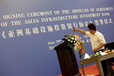 Рабочий украшает сцену для церемонии подписания соглашения о создании Азиатского банка инфраструктурных инвестиций в Пекине 29 июня 2015 года. Китай получит 30,34 процента в Азиатском банке инфраструктурных инвестиций (АБИИ), сообщило в понедельник министерство финансов, что сделает КНР крупнейшим акционером этого института и даст ему право вето по ряду ключевых решений, несмотря на заверения Пекина в отсутствии таких полномочий. REUTERS/Jason Lee