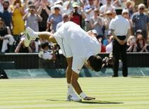 Novak Djokovic toca na grama após vitória sobre Philipp Kohlschreiber na estreia em Wimbledon. 29/06/2015 REUTERS/Suzanne Plunkett